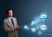 Handsome man typing on smartphone with cloud computing Royalty Free Stock Image