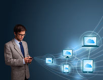 Handsome man typing on smartphone with cloud computing Royalty Free Stock Photography