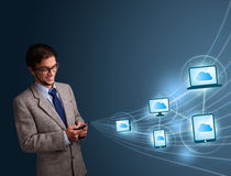 Handsome man typing on smartphone with cloud computing Royalty Free Stock Photo