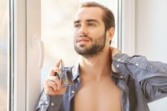 Handsome man in unbuttoned shirt and with bottle. Of perfume near window Royalty Free Stock Photography