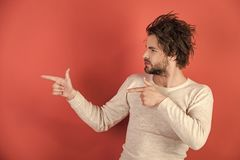 Handsome man with uncombed hair presenting product in underwear. On red background, morning, single, copy space Royalty Free Stock Photography