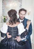 Handsome man untying corset of woman in medieval dress Royalty Free Stock Photo