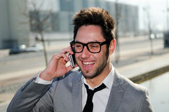 Handsome man in urban background talking on phone. Portrait of handsome man in urban background talking on phone Royalty Free Stock Photos