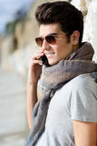 Handsome man in urban background talking on phone. Portrait of handsome man in urban background talking on phone Royalty Free Stock Photo