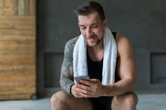 Handsome man use mobile phone in gym Stock Photo