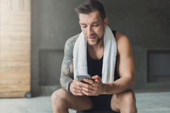Handsome man use mobile phone in gym. Handsome athletic man in gym, use mobile phone, surfing internet social network. Guy with towel rest after exercise in Royalty Free Stock Image