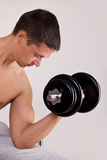 Handsome man uses dumbbells Royalty Free Stock Photography