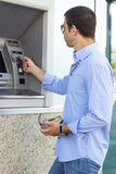 Handsome man using atm Stock Images