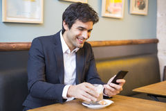 Handsome man using a cell phone in coffee bar Royalty Free Stock Images
