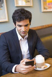 Handsome man using a cell phone in coffee Stock Photography