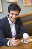 Handsome man using a cell phone in coffee Royalty Free Stock Photo