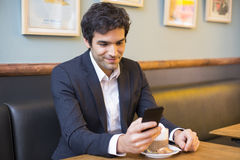 Handsome man using a cell phone in coffee Royalty Free Stock Images