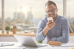Handsome man using cellphone. Portrait of handsome european man using cellphone while sitting at office table with laptop computer and other items Stock Images