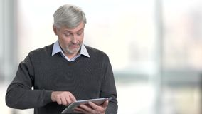 Handsome man using digital tablet on blurred background. Mature caucasian man holding computer tablet at workplace. Man surfing internet stock video footage