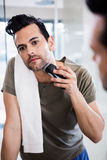 Handsome man using electric razor. In the bathroom Royalty Free Stock Photo