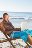 Handsome man using his laptop sitting on his deck chair Royalty Free Stock Images