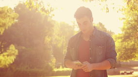 Handsome man using his smartphone in the park stock footage