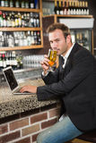 Handsome man using laptop computer and drinking a beer Stock Photography