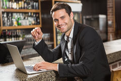 Handsome man using laptop computer. In a pub Stock Images