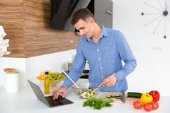 Handsome man using laptop and cooking on the kitchen Stock Photo
