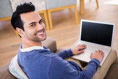 Handsome man using laptop on couch Royalty Free Stock Image