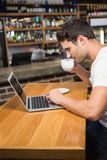Handsome man using laptop and having coffee Royalty Free Stock Image
