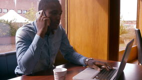 Handsome man using laptop and having a phone call. Sitting in bar stock video footage