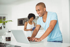 Handsome man using laptop in the kitchen Stock Photography