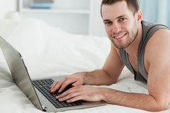 Handsome man using a laptop while lying on his belly Stock Photos