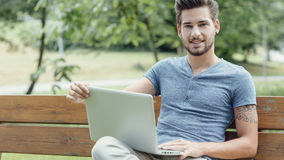 Handsome man using a laptop in the park. Young handsome man relaxing at the park, sitting on a wooden bench and using a laptop Royalty Free Stock Photo