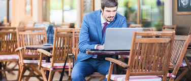 Handsome man using laptop at sidewalk cafe outdoors Stock Images