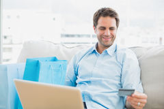 Handsome man using laptop sitting on sofa shopping online Stock Image
