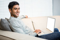 Handsome man using laptop on sofa. In living room Stock Image