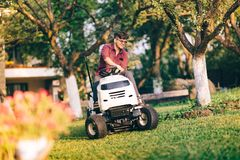 Handsome man using lawn mower and cutting grass in home, residential garden. Smiling handsome man using lawn mower and cutting grass in home, residential garden Stock Photography