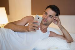 Handsome man using a mobile phone in the white bed. Handsome man using a mobile phone in the beddrom white bed Stock Image