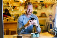Handsome man using mobile phone in coffee shop. Cheerful handsome man using mobile phone in coffee shop Royalty Free Stock Images
