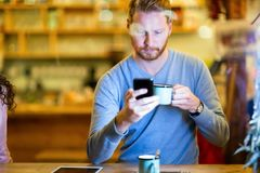 Handsome man using mobile phone in coffee shop. Young handsome man using mobile phone in coffee shop Royalty Free Stock Images