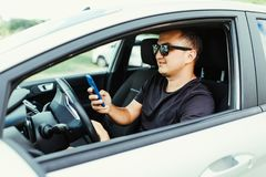 Handsome Young Man using mobile phone while driving a car stock image