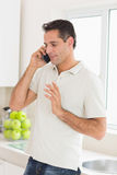 Handsome man using mobile phone in kitchen Royalty Free Stock Photo