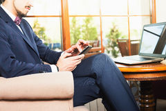 Handsome man using a mobile phone and laptop at cafe. Closeup image handsome man using a mobile phone and laptop at cafe or restaurant. Businessman dressed in Stock Photo