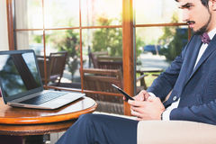 Handsome man using a mobile phone and laptop at cafe Royalty Free Stock Image