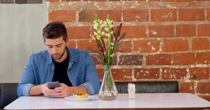 Handsome man using mobile phone at table 4k. Handsome man using mobile phone at table in cafe 4k stock video