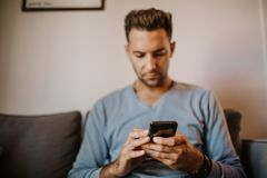 Handsome man using mobile smartphone for surfing web internet and sending audio message. Man using gadget at modern. Apartment stock photo