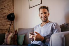 Handsome man using mobile smartphone for surfing web internet and sending audio message. Man using gadget at modern. Apartment royalty free stock photo
