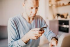 Handsome man using mobile smartphone for surfing web internet and sending audio message. Man using gadget at modern. Apartment royalty free stock images