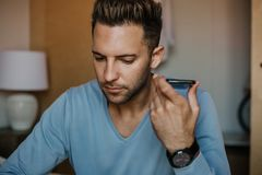 Handsome man using mobile smartphone for surfing web internet and sending audio message. Man using gadget at modern. Apartment stock photos