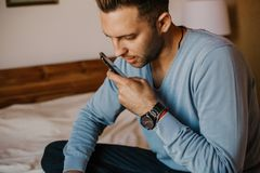 Handsome man using mobile smartphone for surfing web internet and sending audio message. Man using gadget at modern. Apartment royalty free stock image