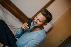 Handsome man using mobile smartphone for surfing web internet and sending audio message. Man using gadget at modern. Apartment stock images
