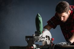 Handsome man using modern electric circular saw in the workshop. Handsome man using modern electric circular saw for ctting wood  in the workshop royalty free stock photography