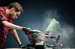 Handsome man using modern electric circular saw in the workshop. Handsome man using modern electric circular saw for ctting wood  in the workshop stock images